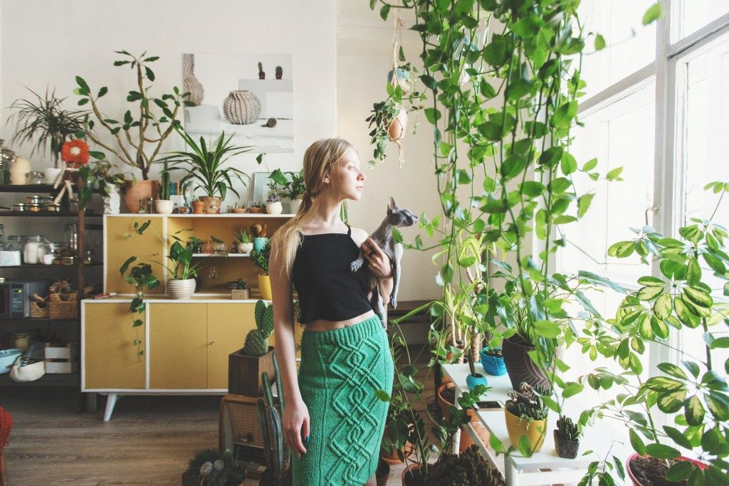 Woman surrounded by plants in the living room
